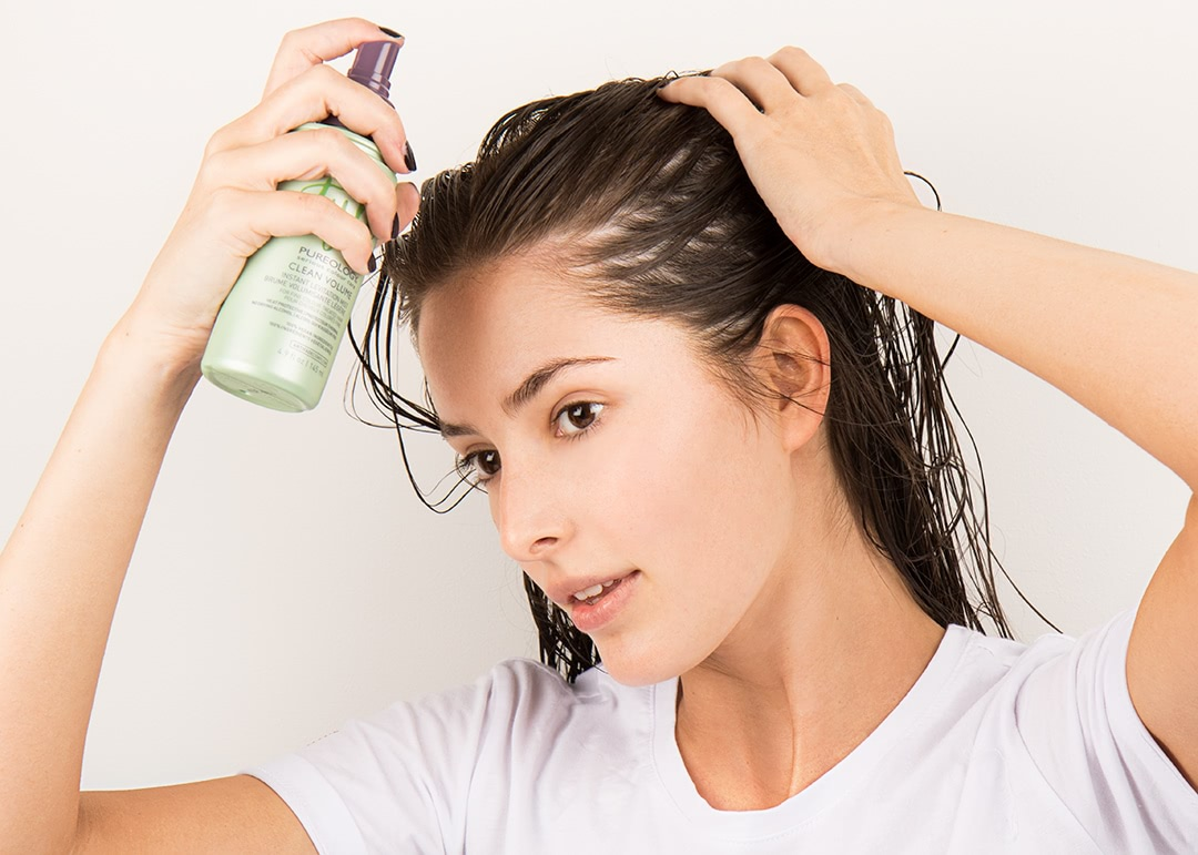 model with wet hair applying styling product